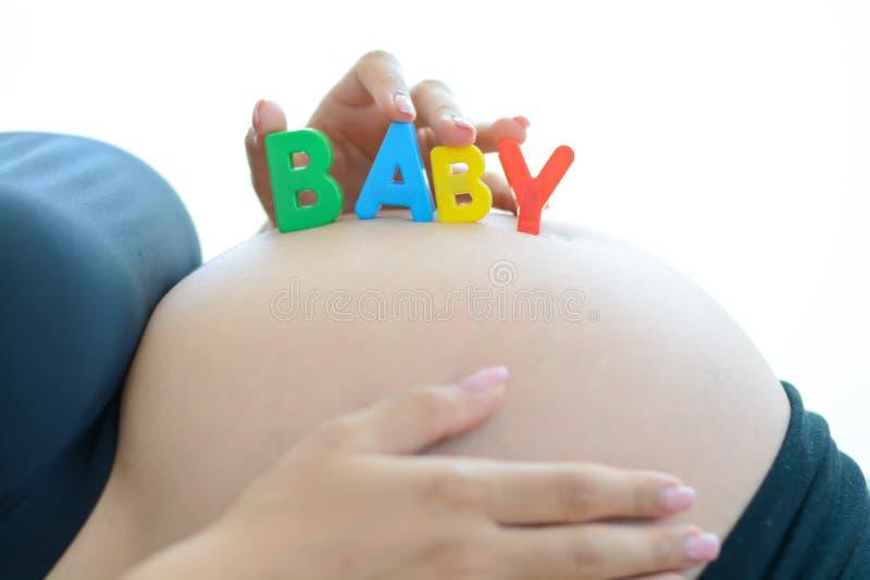Jonge aanstaande moeder die met brievenblokken baby op haar zwangere buik spellen stock foto