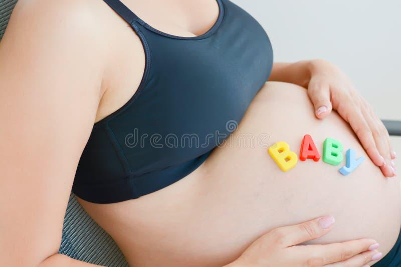 Jonge aanstaande moeder die met brievenblokken baby op haar zwangere buik spellen royalty-vrije stock foto