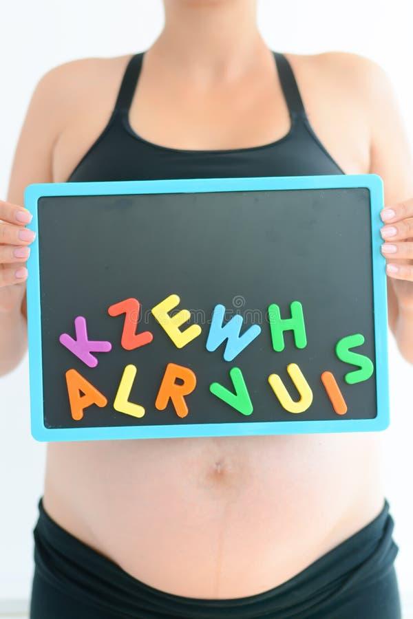 Jonge aanstaande moeder met magnetische brievenblokken die een naam voor haar baby proberen te kiezen stock fotografie