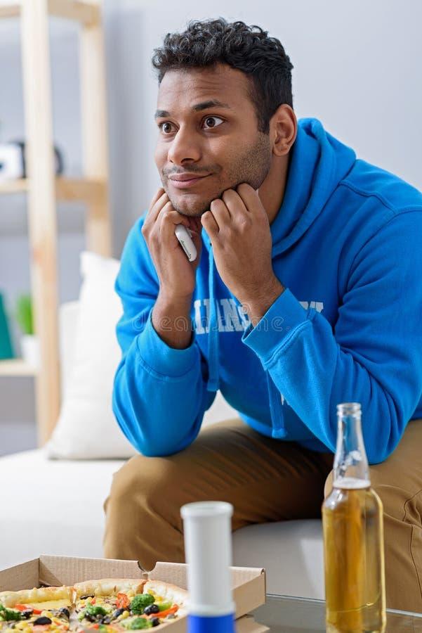 Jonge aantrekkelijke Afrikaanse mens het letten op televisie royalty-vrije stock fotografie
