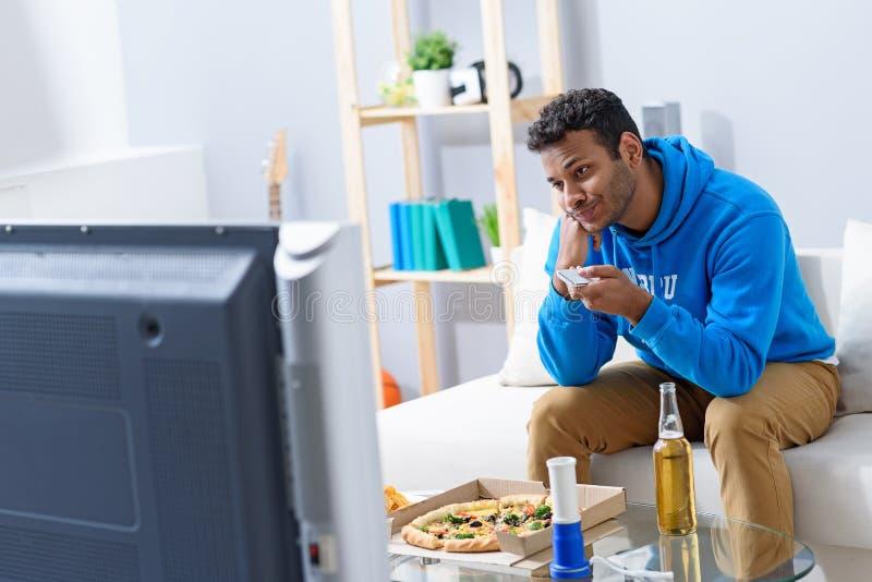 Jonge aantrekkelijke Afrikaanse mens het letten op televisie stock afbeelding