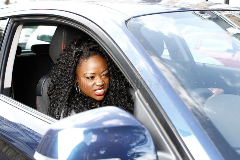 Jonge aantrekkelijke Afrikaanse vrouw die haar auto drijven stock afbeelding
