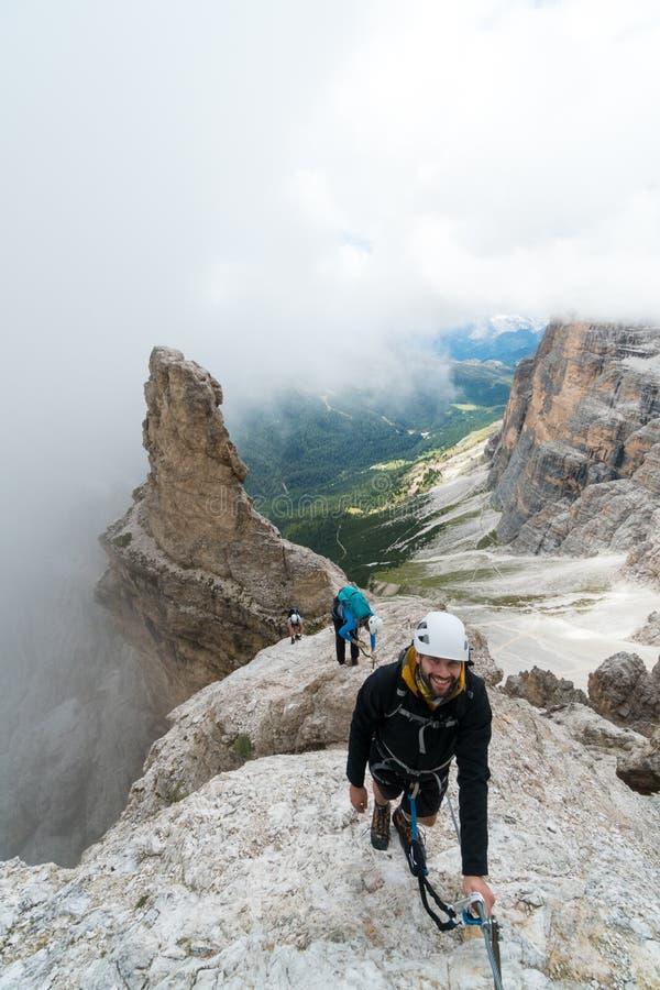 Jonge aantrekkelijke alpinisten op zeer blootgesteld via Ferrata in het Dolomiet van Italië stock afbeelding