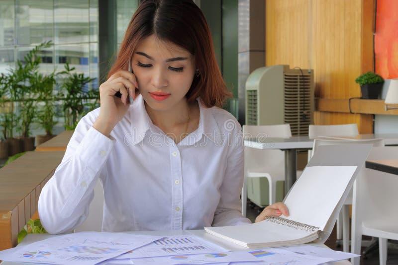 Jonge aantrekkelijke Aziatische bedrijfsvrouw die met mobiele telefoon, grafiek in bureau werken stock afbeelding