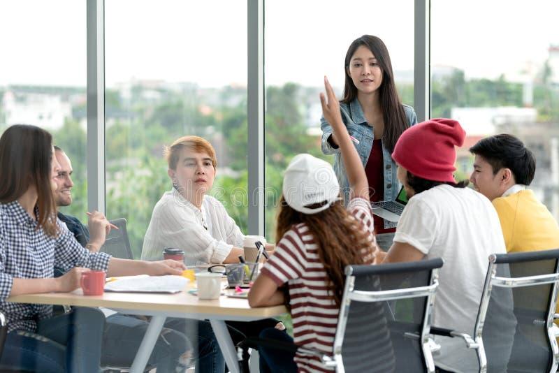 Jonge aantrekkelijke Aziatische creatieve hipster vrouwelijke leider die zich bij moderne van de bureau gelukkige het spreken en  royalty-vrije stock afbeelding