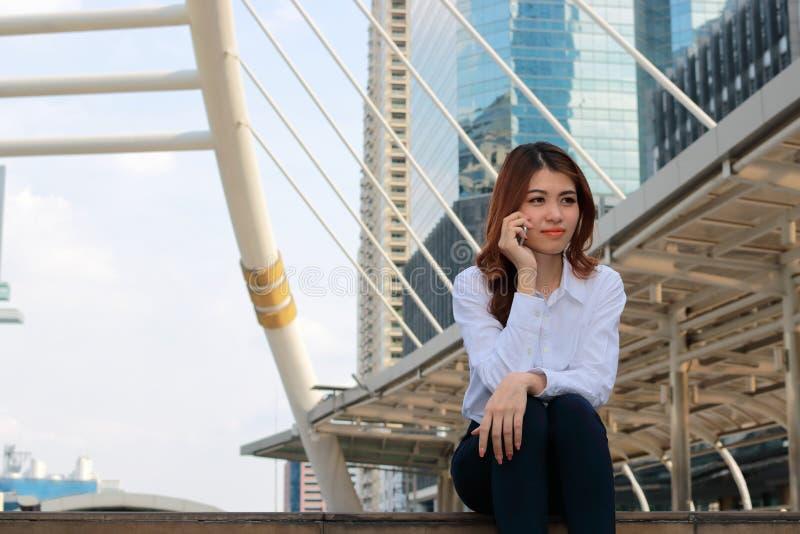 Jonge aantrekkelijke Aziatische dame die op telefoon bij de stedelijke bouw met exemplaar ruimteachtergrond spreken stock afbeeldingen