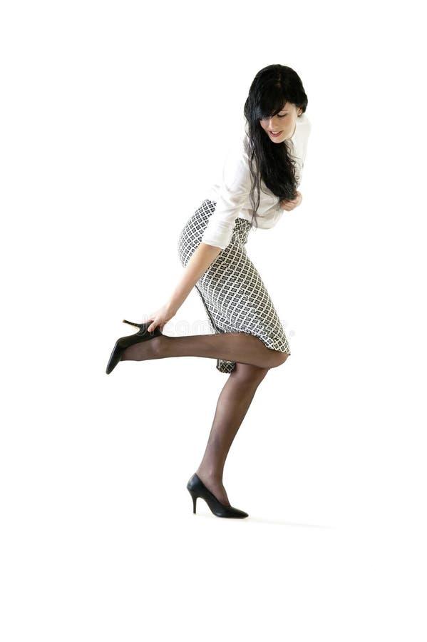 Jonge aantrekkelijke bedrijfsvrouw die haar schoen aanpast stock foto