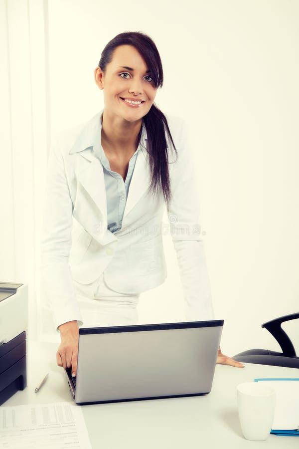 Jonge aantrekkelijke bedrijfsvrouw die laptop met behulp van op het kantoor royalty-vrije stock afbeeldingen