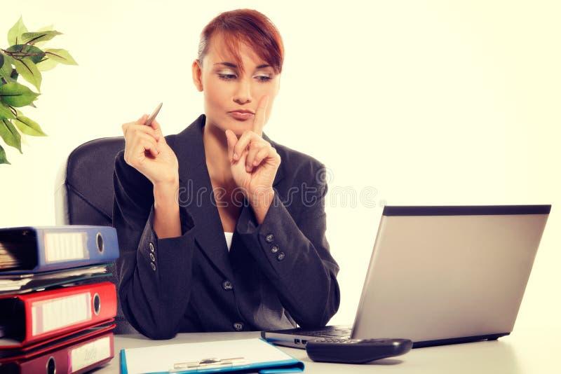 Jonge aantrekkelijke bedrijfsvrouw die laptop met behulp van op het kantoor stock afbeelding