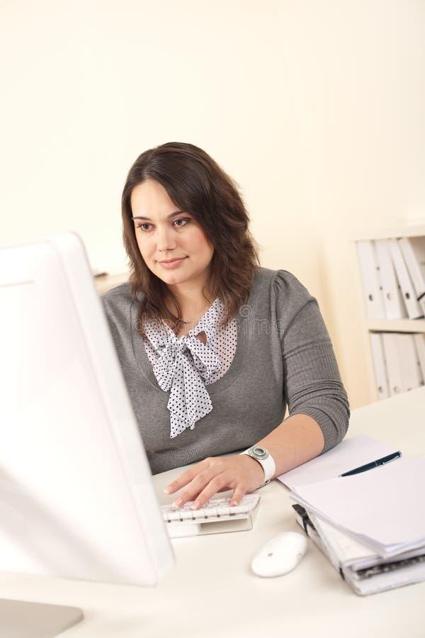 Jonge aantrekkelijke bedrijfsvrouw die op kantoor werkt stock foto
