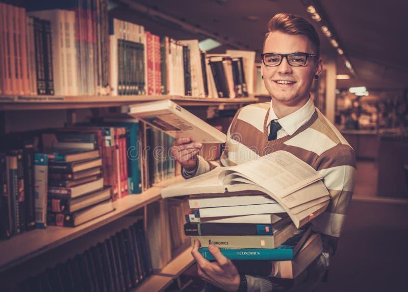 Jonge aantrekkelijke bibliothecaris die een stapel van boeken in de universitaire bibliotheek houden stock foto's