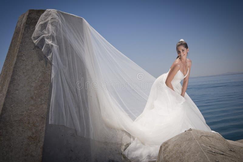 Jonge aantrekkelijke bruid in kleding die zich door concrete kolommen bevinden royalty-vrije stock fotografie