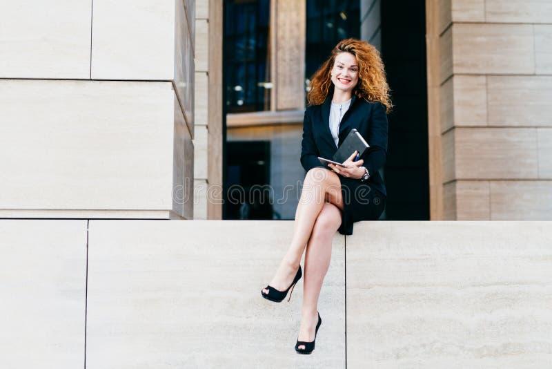 Jonge aantrekkelijke dame met krullend haar, die zwarte formele kostuum en schoenen met hoge hielen dragen, houdend haar notitieb stock foto's