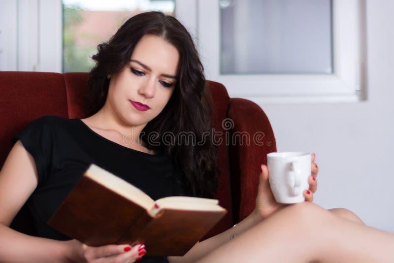 Jonge aantrekkelijke de koffiekop van de vrouwenholding op benen en lezingsboek royalty-vrije stock afbeeldingen