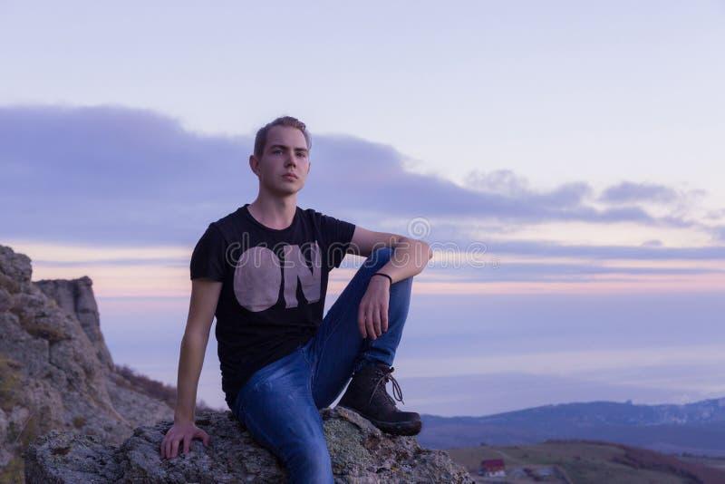 Jonge aantrekkelijke die mens met op de bovenkant van bergen tegen de achtergrond van een purpere zonsondergang wordt gevestigd stock foto's
