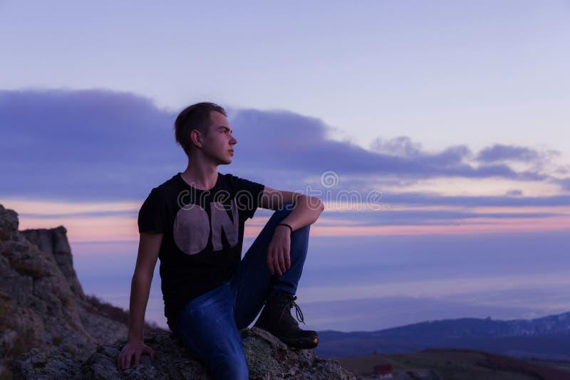 Jonge aantrekkelijke die mens met op de bovenkant van bergen tegen de achtergrond van een purpere zonsondergang wordt gevestigd stock afbeeldingen