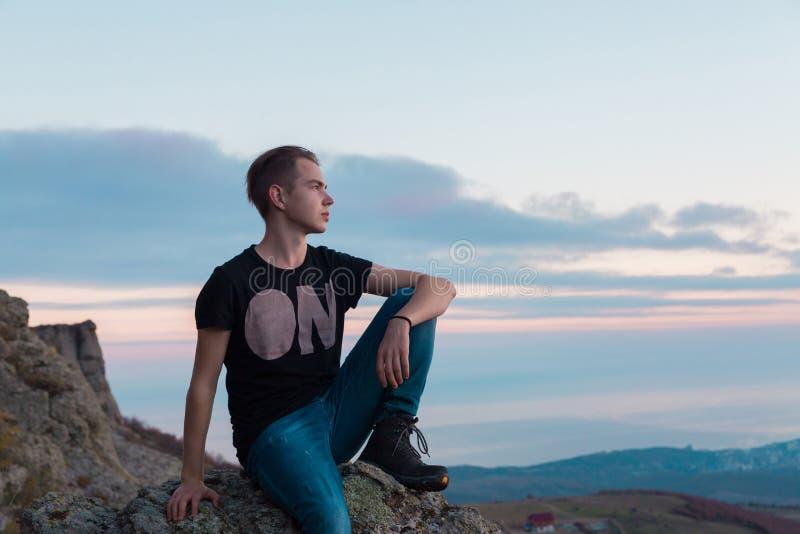 Jonge aantrekkelijke die mens met op de bovenkant van bergen tegen de achtergrond van een roze zonsondergang wordt gevestigd stock afbeeldingen