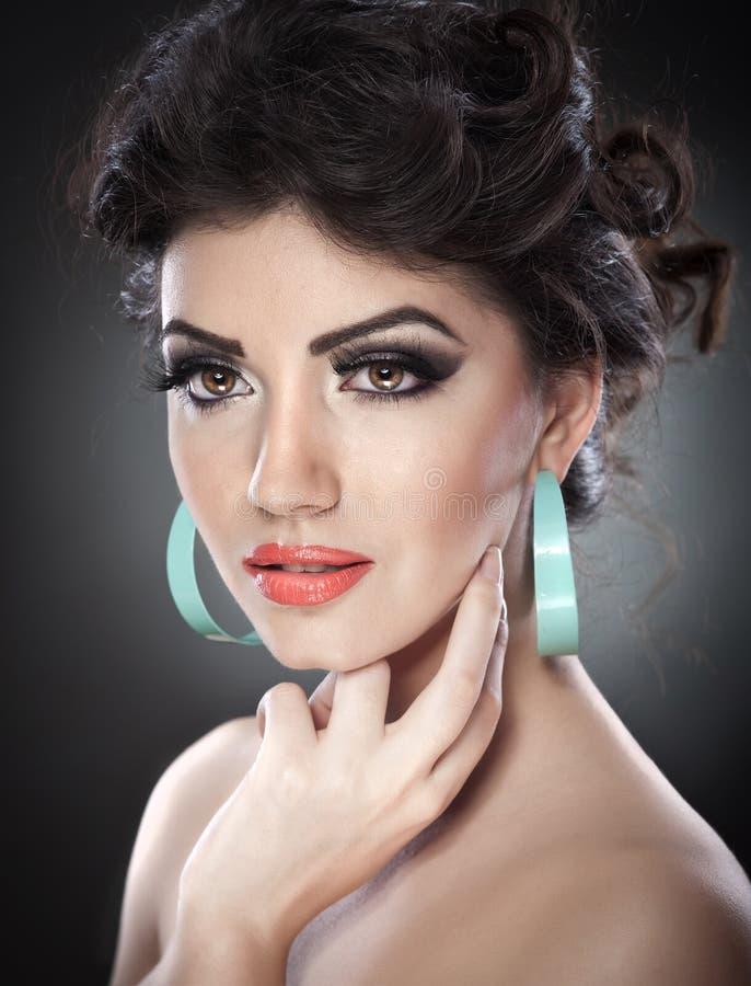 Jonge aantrekkelijke donkerbruine dame met creatieve make-up en het mooie kapsel stellen op grijze achtergrond in studio Dicht Po stock afbeelding