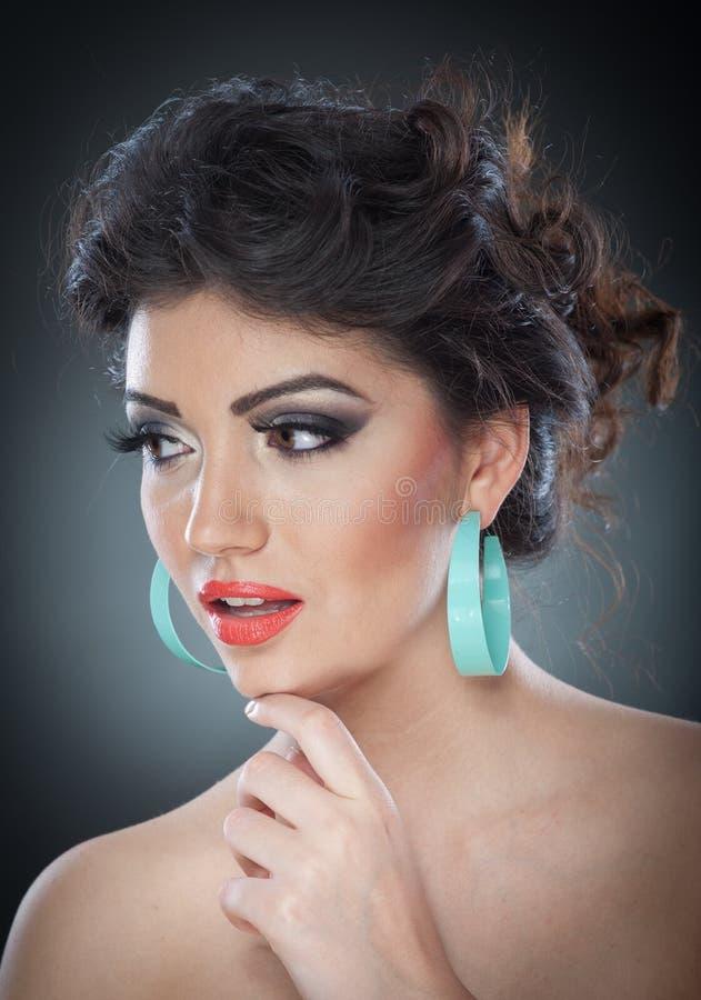Jonge aantrekkelijke donkerbruine dame met creatieve make-up en het mooie kapsel stellen op grijze achtergrond in studio Dicht Po stock foto