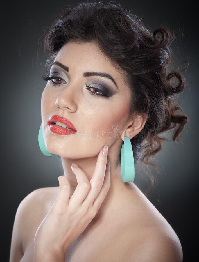 Jonge aantrekkelijke donkerbruine dame met creatieve make-up en het mooie kapsel stellen op grijze achtergrond in studio Dicht Po royalty-vrije stock foto's