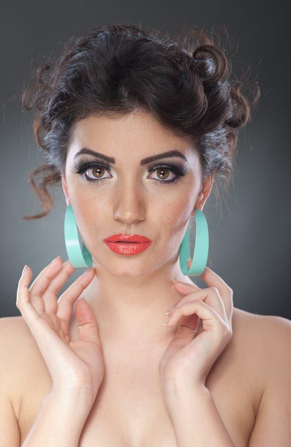 Jonge aantrekkelijke donkerbruine dame met creatieve make-up en het mooie kapsel stellen op grijze achtergrond in studio Dicht Po royalty-vrije stock afbeeldingen