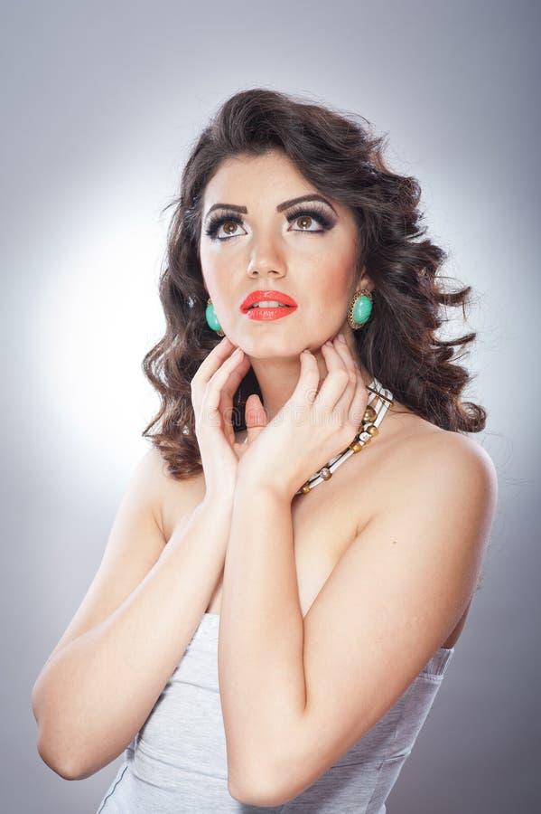 Jonge aantrekkelijke donkerbruine dame met make-up en het mooie kapsel stellen op grijze achtergrond in studio stock foto's