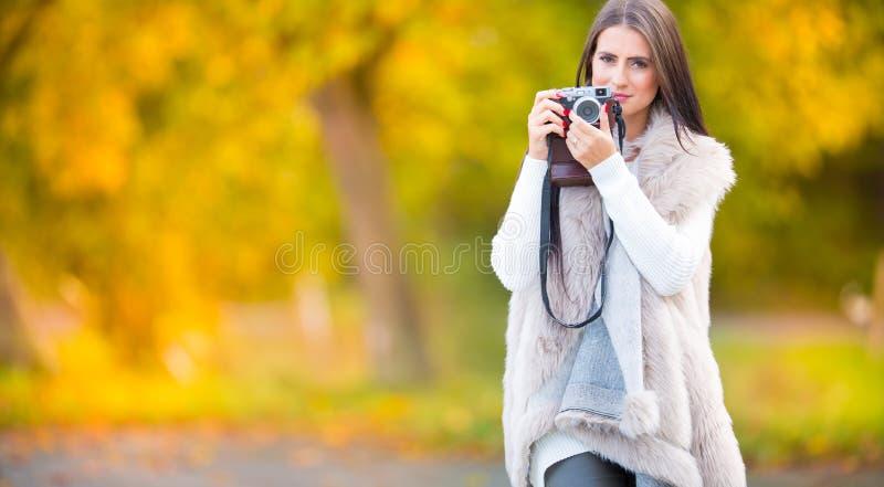 Jonge aantrekkelijke donkerbruine vrouw die de retro camera in openlucht houden in Mooi jong meisje die met retro camera in autum royalty-vrije stock afbeeldingen