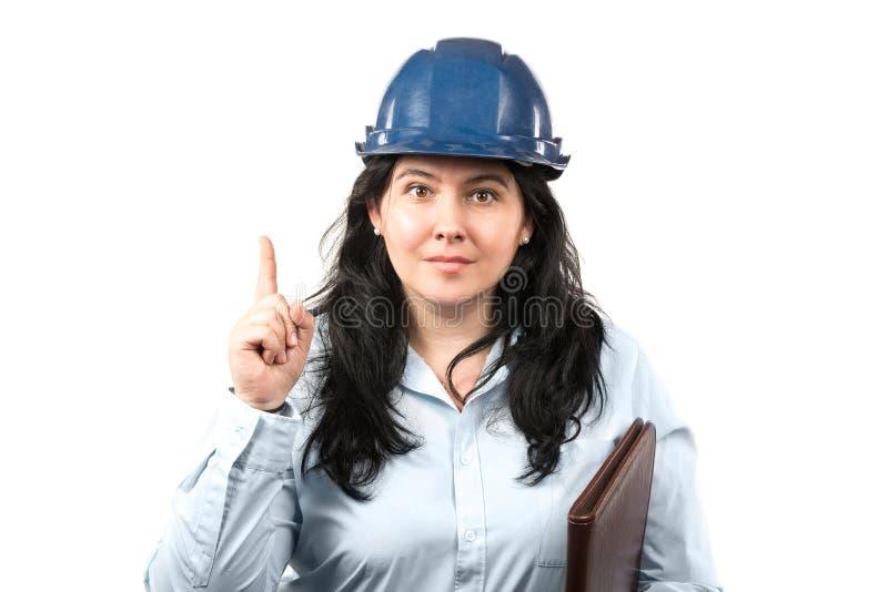 Jonge aantrekkelijke donkerbruine vrouweningenieur of architect met blauwe veiligheidshoed die wijzervinger tonen die op witte ac stock fotografie
