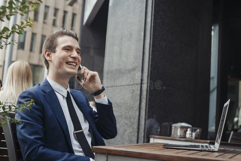 Jonge aantrekkelijke donkerbruine zakenman die door mobiele telefoon en te glimlachen spreken royalty-vrije stock foto's
