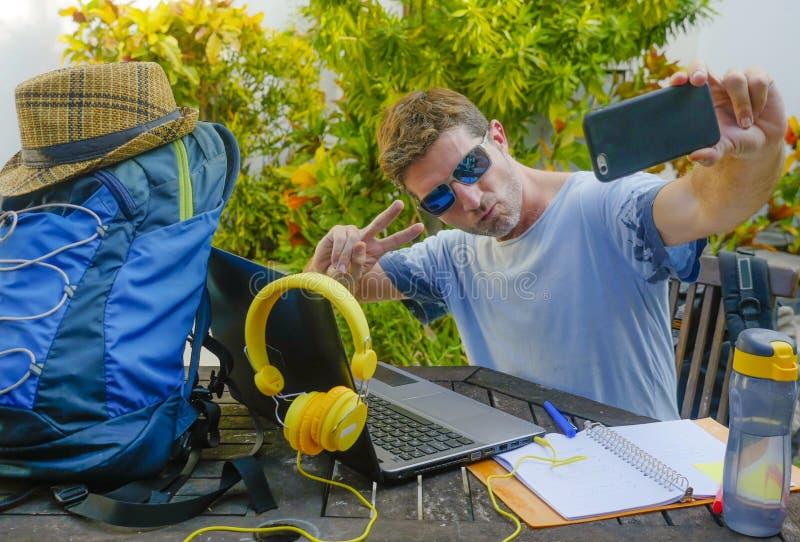 Jonge aantrekkelijke en gelukkige digitale nomademens die in openlucht met laptop computer vrolijke nemende selfie pic werken met stock foto