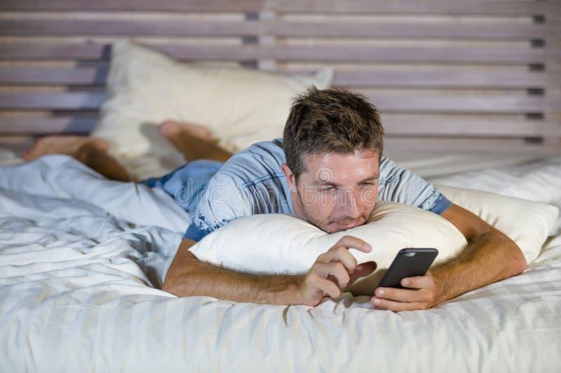 Jonge aantrekkelijke en gelukkige mens die op bed die de mobiele telefoon die van Internet met behulp van verzendend tekst in soc stock fotografie