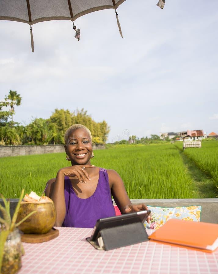 Jonge aantrekkelijke en gelukkige zwarte afro Amerikaanse vrouw die online met digitale tabletstootkussen het drinken kokosnotenz royalty-vrije stock foto's