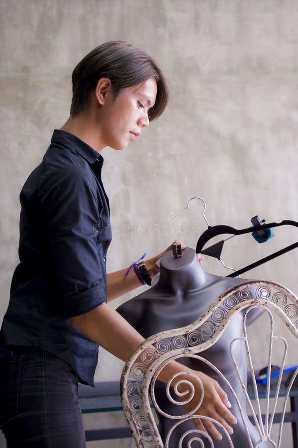 Jonge aantrekkelijke en koele Aziatische de opslageigenaar of werknemer die van de mensenkleding bij de winkel werken die van de  royalty-vrije stock foto
