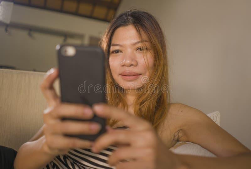 Jonge aantrekkelijke en ontspannen jaren '30 Aziatische Indonesische vrouw die comfortabel met het mobiele de laag van de telefoo royalty-vrije stock foto