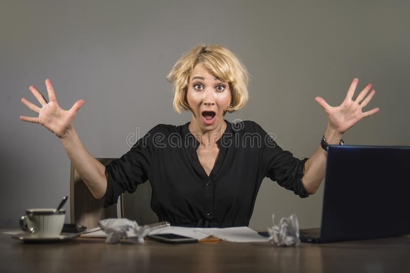 Jonge aantrekkelijke en wanhopige bedrijfsvrouw die met laptop computerzitting bij bureau werken die ziek en overweldigd s gillen royalty-vrije stock foto's