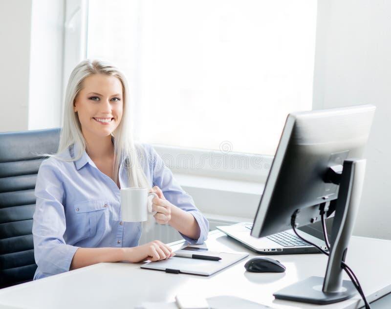 Jonge, aantrekkelijke en zekere bedrijfsvrouw die in bureau werken stock foto