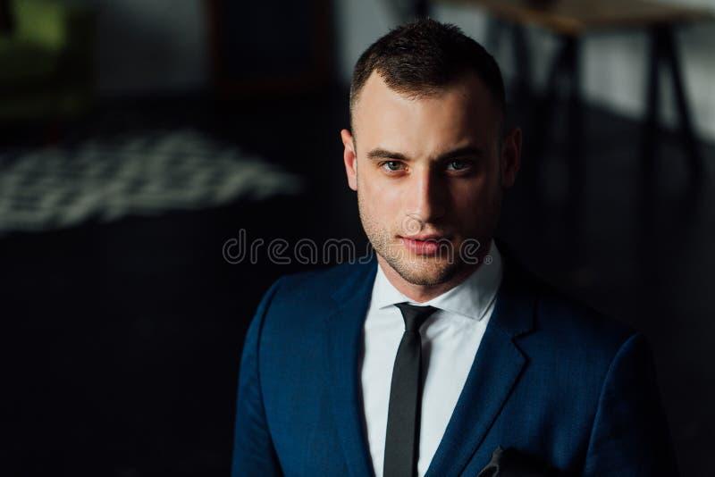 Jonge aantrekkelijke en zekere zakenman in blauwe kostuum en avondkleding stock afbeeldingen