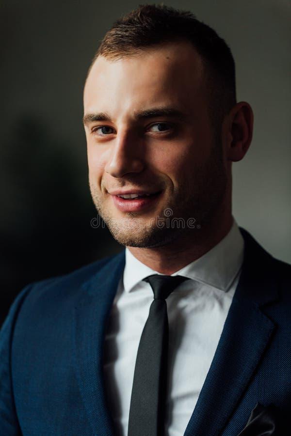 Jonge aantrekkelijke en zekere zakenman in blauwe kostuum en avondkleding stock foto