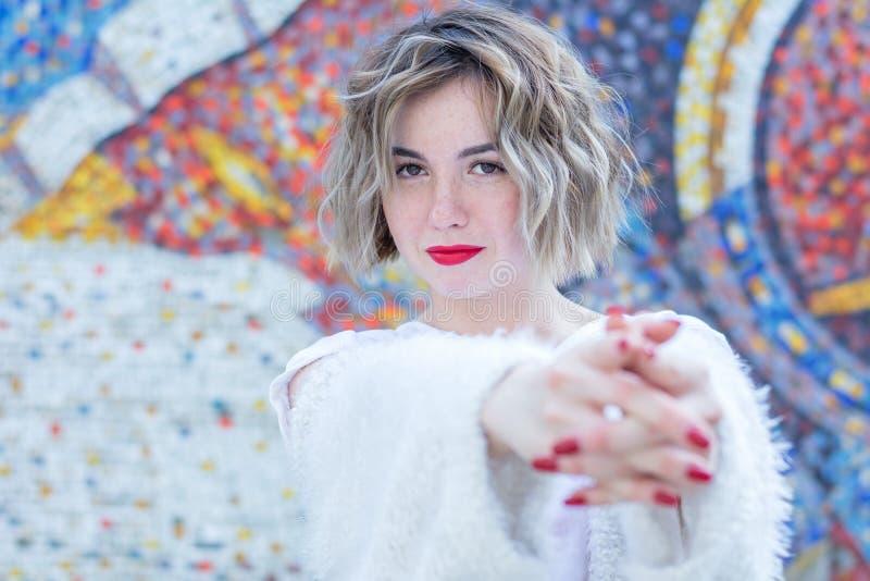 Jonge aantrekkelijke freckled vrouw die met rode lippen in witte vrijetijdskleding het stellen in de straat lopen royalty-vrije stock fotografie