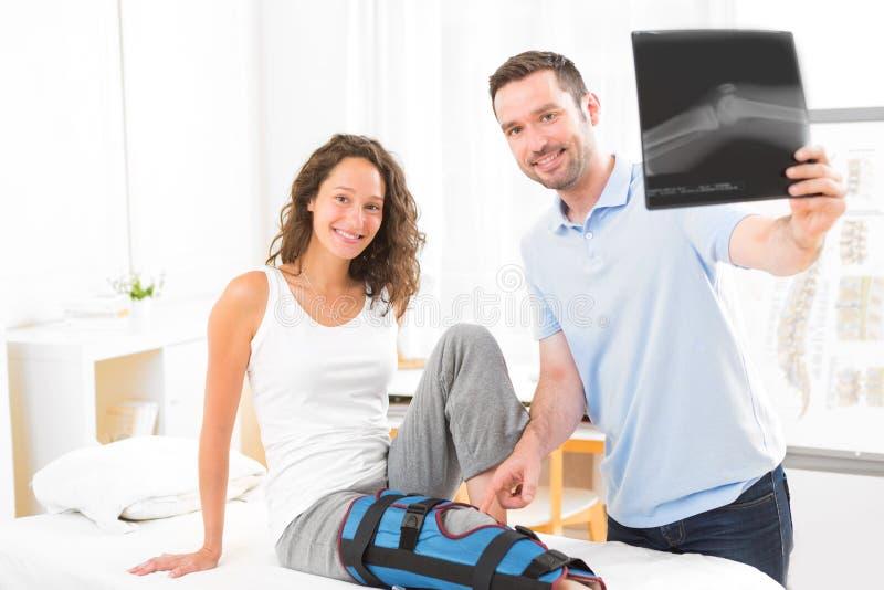 Jonge aantrekkelijke fysiotherapeut die Röntgenstraal met patiënt analyseren stock afbeelding