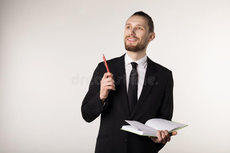Jonge aantrekkelijke gebaarde leraar in zwart kostuum en bandholdingsnotitieboekje en pen in handen royalty-vrije stock foto