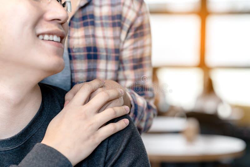 Jonge aantrekkelijke gelukkige Aziatische man en vrouwenholdingshanden op schouder die en samen met liefde en zorg bij koffie bek royalty-vrije stock fotografie