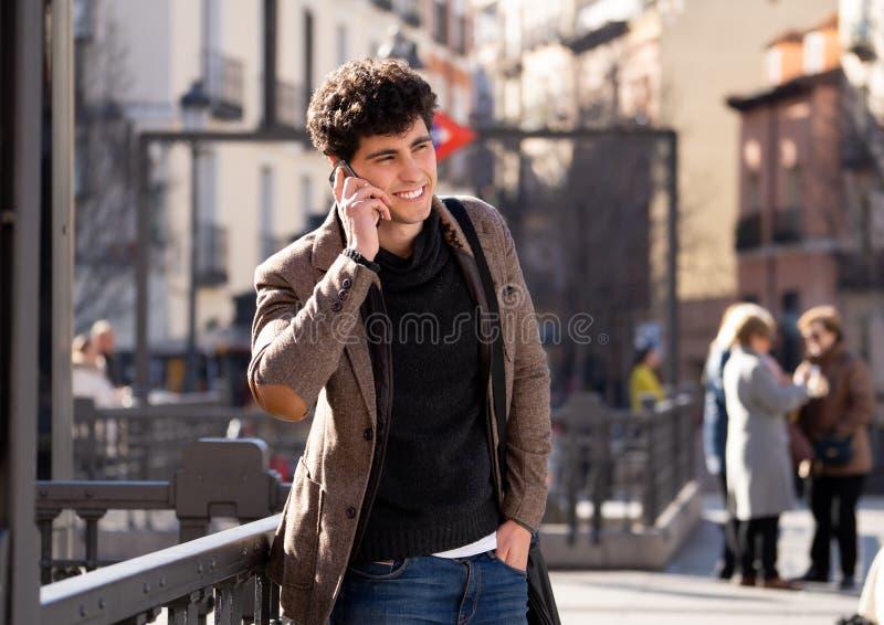 Jonge aantrekkelijke gelukkige mens die op smartphone in Europese stad spreken royalty-vrije stock foto's