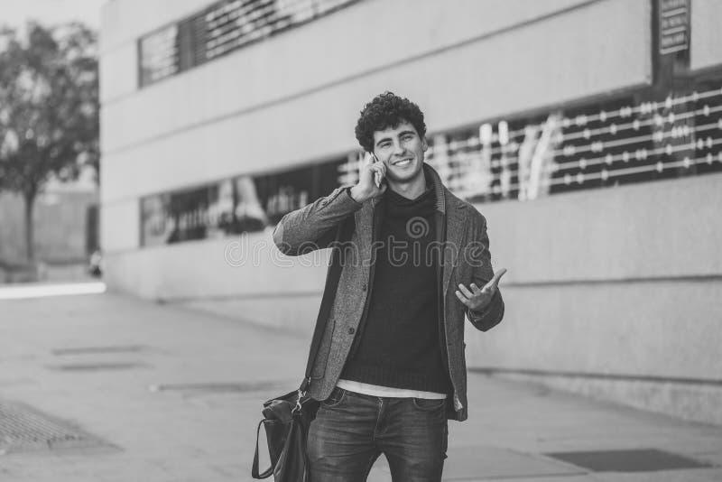 Jonge aantrekkelijke gelukkige mens die op smartphone in Europese stad spreken royalty-vrije stock foto