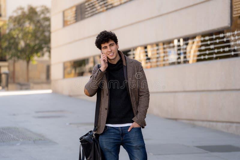 Jonge aantrekkelijke gelukkige mens die op smartphone in Europese stad spreken stock afbeeldingen