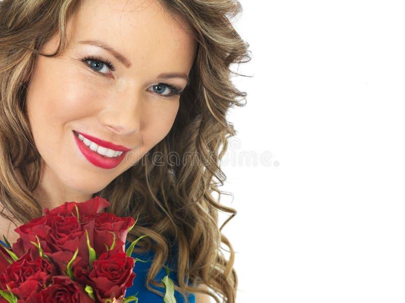 Jonge Aantrekkelijke Gelukkige Vrouw die een Bos van Rode Rozen houden stock foto