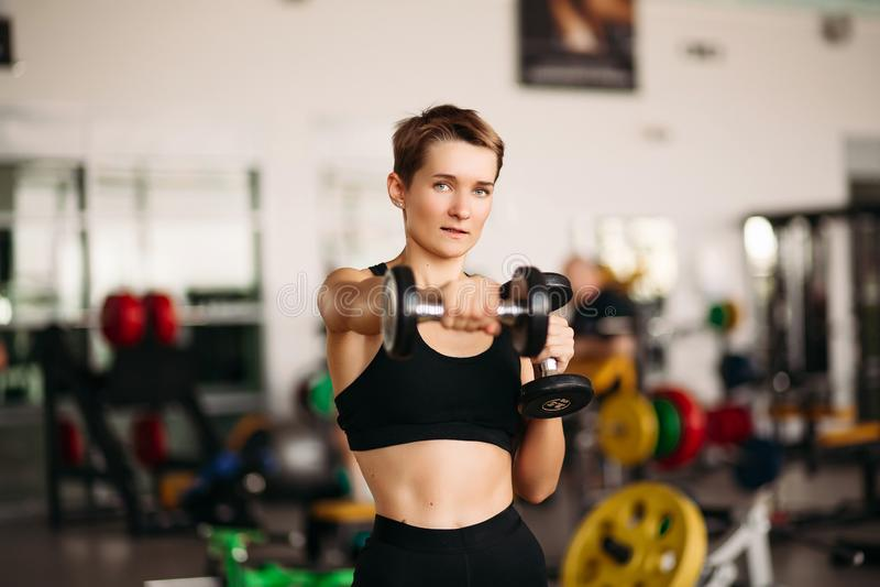 Jonge aantrekkelijke geschiktheidsmeisje het opheffen domoorgewichten voor lichaam in gymnastiek stock afbeeldingen