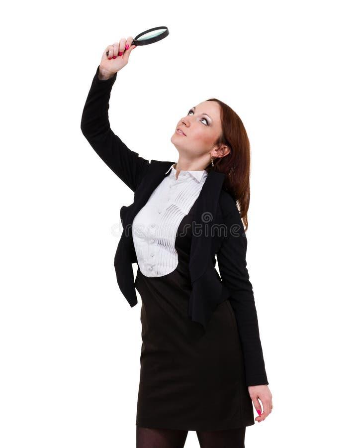 Jonge aantrekkelijke glimlachende bedrijfsvrouw die die een vergrootglas onderzoeken, op wit wordt geïsoleerd stock afbeeldingen