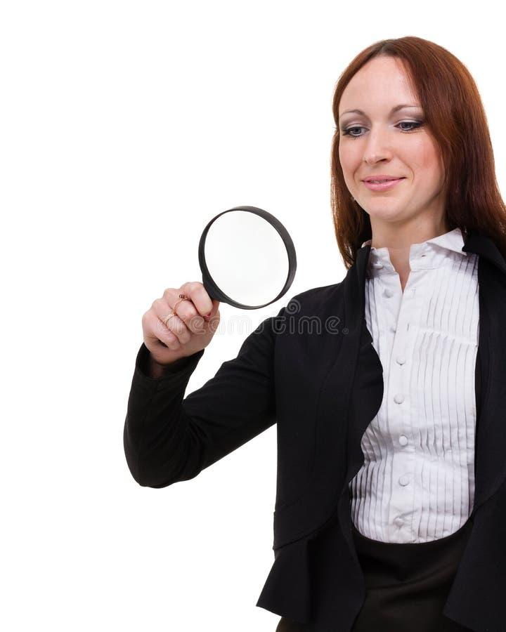 Jonge aantrekkelijke glimlachende bedrijfsvrouw die die een vergrootglas onderzoeken, op wit wordt geïsoleerd stock afbeelding