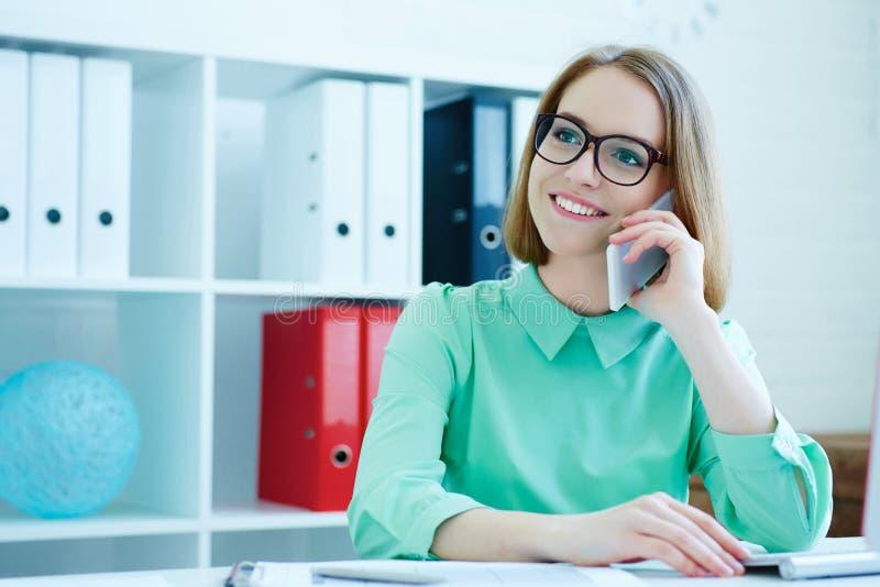 Jonge aantrekkelijke glimlachende bedrijfsvrouw die in glazen bij bureaustoel zitten die bij bureaucomputer die aan mobiel werken stock afbeelding